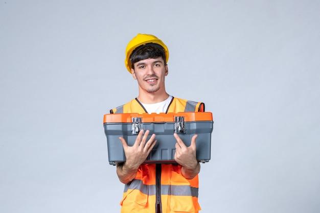Vooraanzicht jonge mannelijke werknemer met gereedschapskist op witte achtergrond