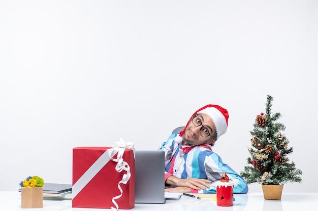 Vooraanzicht jonge mannelijke werknemer zittend op zijn werkplek op witte achtergrond