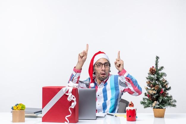 Vooraanzicht jonge mannelijke werknemer zittend op zijn werkplek verward op witte achtergrond