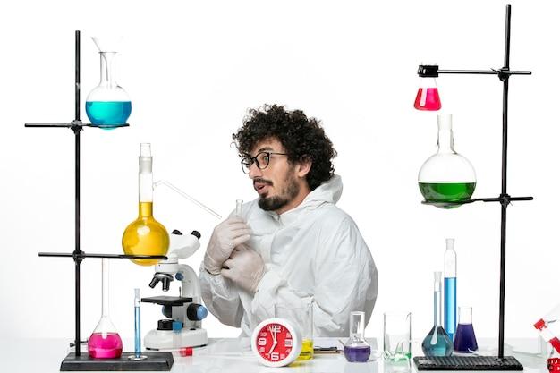 Vooraanzicht jonge mannelijke wetenschapper in de speciale kolf van de kostuumholding met oplossing op lichte witte muur