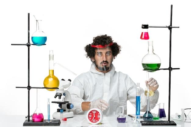 Vooraanzicht jonge mannelijke wetenschapper in speciaal pak die beschermende helm draagt en aan witte muur werkt