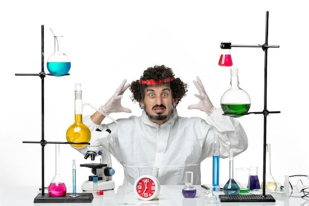 Vooraanzicht jonge mannelijke wetenschapper in speciaal pak en het dragen van beschermende helm