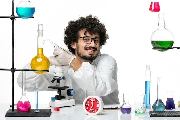 Vooraanzicht jonge mannelijke wetenschapper in speciaal pak knuffelen microscoop en glimlachend op witte muur