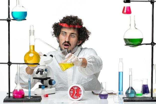Vooraanzicht jonge mannelijke wetenschapper in speciaal pak met beschermende helm met behulp van microscoop op lichtwitte muur science lab covid-chemie man