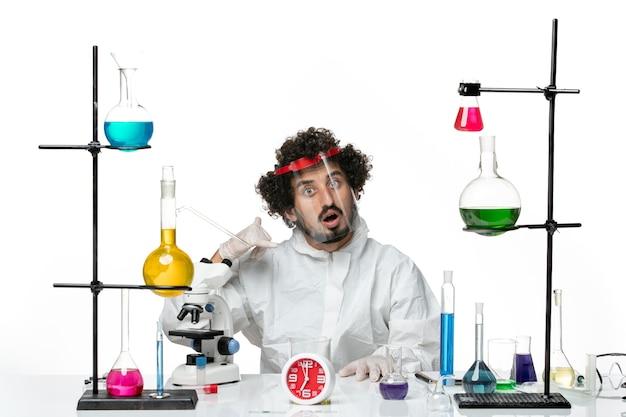 Vooraanzicht jonge mannelijke wetenschapper in speciaal pak met speciale beschermende helm op witte achtergrond