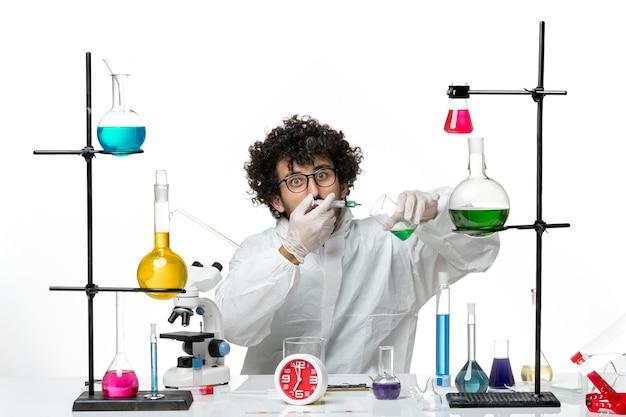 Vooraanzicht jonge mannelijke wetenschapper in speciaal pak werken met injectie en oplossing op de witte achtergrond