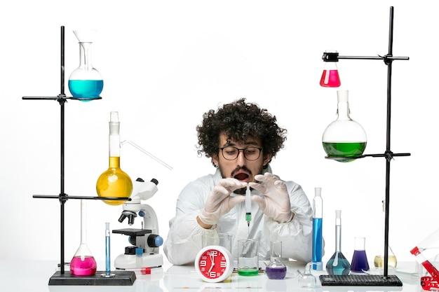Vooraanzicht jonge mannelijke wetenschapper in speciaal pak werken met injectie en oplossing op witte muur