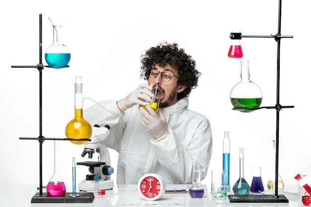 Vooraanzicht jonge mannelijke wetenschapper in speciaal pak zittend met oplossingen drinken op witte muur