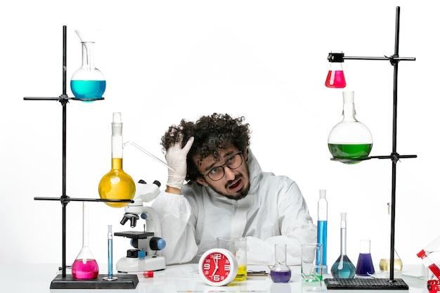 Vooraanzicht jonge mannelijke wetenschapper in speciaal pak zittend met oplossingen op witte muur