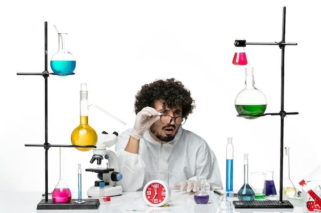 Vooraanzicht jonge mannelijke wetenschapper in wit speciaal pak zitten met oplossingen kijken naar iets op witte muur science lab covid mannelijke chemie