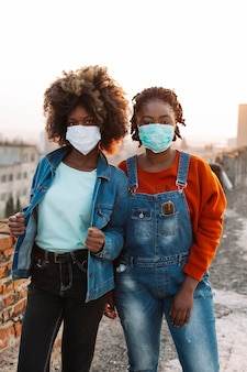 Vooraanzicht jonge meisjes die met medische maskers stellen