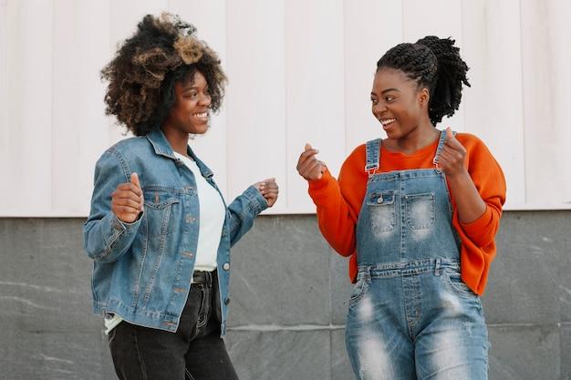 Vooraanzicht jonge meisjes glimlachen naar elkaar