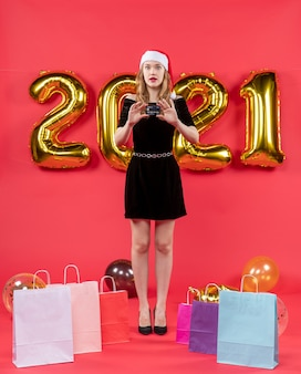 Vooraanzicht jonge mooie dame in zwarte kledingzakken op vloerballons op rood