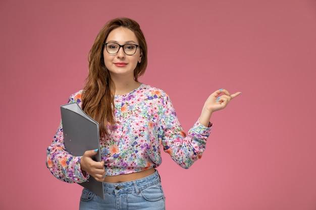 Vooraanzicht jonge mooie vrouw in bloem ontworpen shirt en spijkerbroek met grijze bestanden op de roze achtergrond