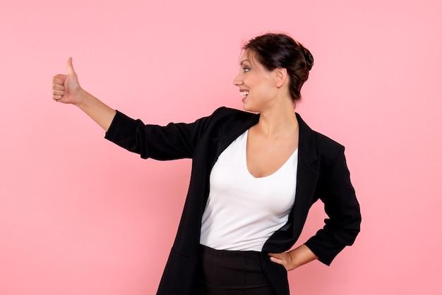 Vooraanzicht jonge mooie vrouw in een donkere jas op de roze achtergrond