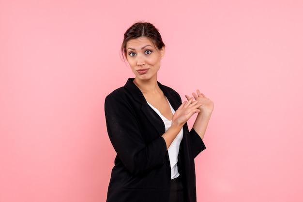 Vooraanzicht jonge mooie vrouw in een donkere jas op de roze achtergrond Gratis Foto