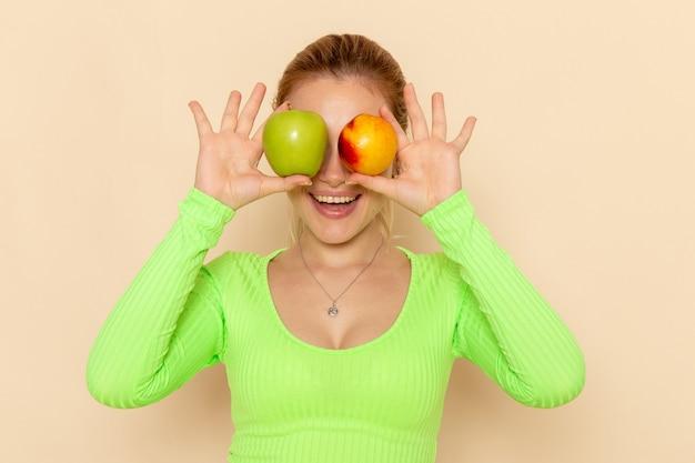 Vooraanzicht jonge mooie vrouw in groen shirt met paar verse appels die haar ogen op crème muur fruit model mellow vrouw bedekken