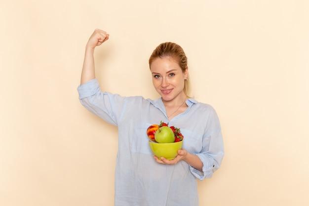 Vooraanzicht jonge mooie vrouw in shirt met plaat met fruit en buigen op de crème muur fruit rijpe model vrouw pose