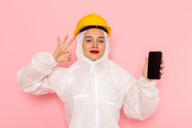 Vooraanzicht jonge mooie vrouw in speciaal wit pak dragen van beschermende helm met telefoon met glimlach op de roze ruimte speciaal pak vrouw