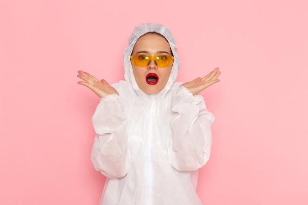 Vooraanzicht jonge mooie vrouw in speciaal wit pak speciale zonnebril dragen met verbaasde uitdrukking op de roze ruimte speciaal pak meisje vrouw