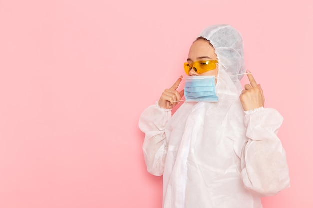 Vooraanzicht jonge mooie vrouw in speciaal wit pak steriel masker dragen op de roze ruimte speciaal pak foto meisje vrouw
