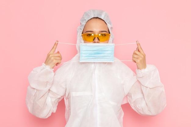 Vooraanzicht jonge mooie vrouw in speciaal wit pak steriel masker dragen op de roze ruimte speciaal pak meisje vrouw