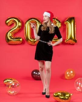 Vooraanzicht jonge mooie vrouw in zwarte jurk ballonnen op rood