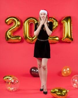 Vooraanzicht jonge mooie vrouw in zwarte jurk die de handen in de lucht steekt met ballonnen op rood