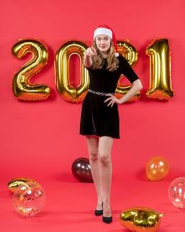Vooraanzicht jonge mooie vrouw in zwarte jurk wijzend op camera ballonnen op rood