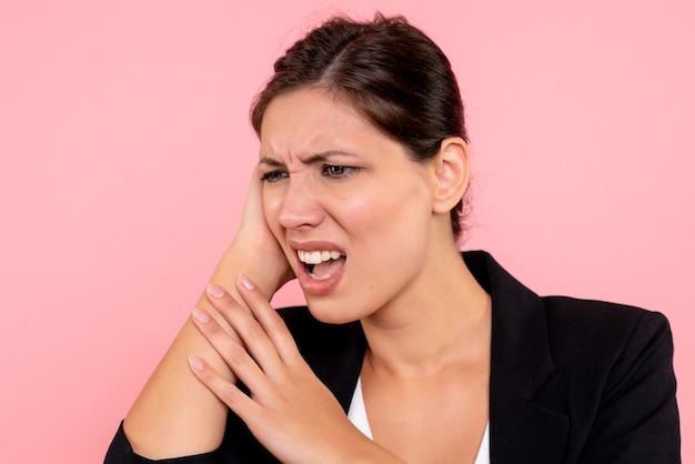 Vooraanzicht jonge mooie vrouw met hoofdpijn op roze achtergrond