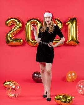 Vooraanzicht jonge mooie vrouw met kerstmuts ballonnen op rood