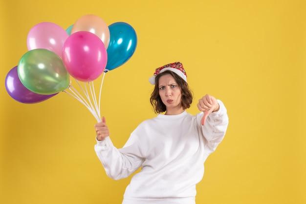 Vooraanzicht jonge mooie vrouw met kleurrijke ballonnen op gele emotie kerst nieuwjaar vrouw kleur