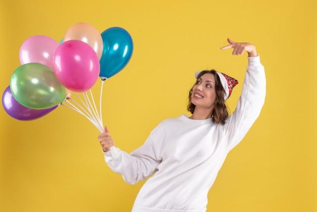 Vooraanzicht jonge mooie vrouw met kleurrijke ballonnen op gele kleur kerstmis nieuwjaar emotie vrouw