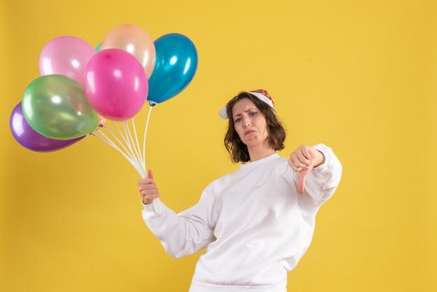 Vooraanzicht jonge mooie vrouw met kleurrijke ballonnen op gele kleur kerstmis nieuwjaar emoties vrouw
