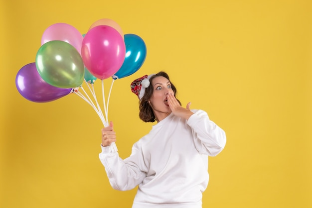 Vooraanzicht jonge mooie vrouw met kleurrijke ballonnen op gele nieuwjaar emotie kerst vrouw kleur