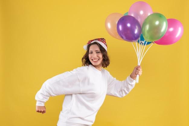 Vooraanzicht jonge mooie vrouw met kleurrijke ballonnen op gele nieuwjaar emotie vrouw kleur xmas