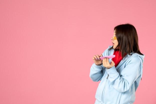 Vooraanzicht jonge mooie vrouw met ooglapjes doet haar nagels op roze achtergrond