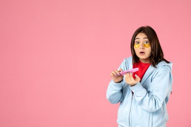 Vooraanzicht jonge mooie vrouw met ooglapjes en nagelvijl op roze achtergrond