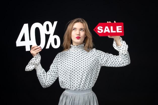 Vooraanzicht jonge mooie vrouw met verkoop schrijven en op de zwarte muur kleur winkelen vakantie xmas emotie mode