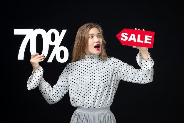 Vooraanzicht jonge mooie vrouw met verkoop schrijven en op zwarte muur kleur winkelen foto emotie schoonheid model xmas