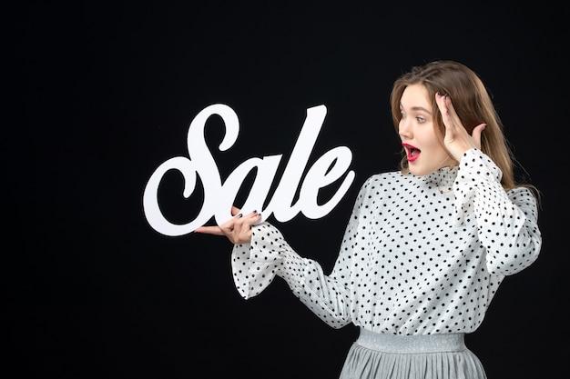 Vooraanzicht jonge mooie vrouw met verkoop schrijven op een zwarte muur winkelen schoonheid mode emotie kleur model foto