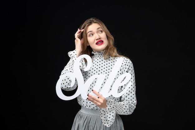 Vooraanzicht jonge mooie vrouw met verkoop schrijven op zwarte muur kleur winkelen mode foto emotie model
