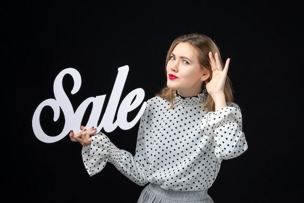 Vooraanzicht jonge mooie vrouw met verkoop schrijven op zwarte muur kleur winkelen schoonheid mode foto emotie