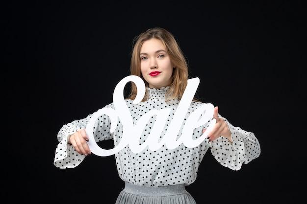 Vooraanzicht jonge mooie vrouw met verkoop schrijven op zwarte muur kleuren winkelen model mode foto emotie schoonheid
