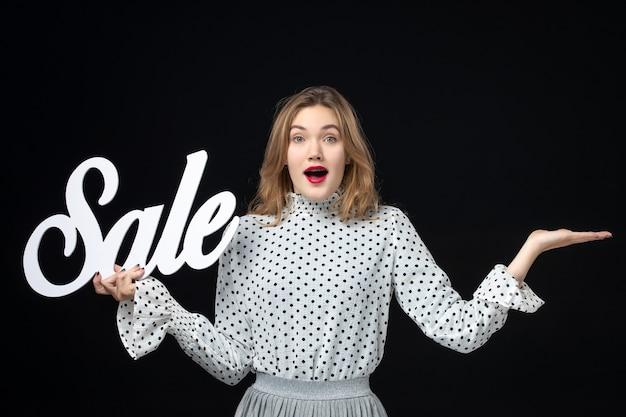 Vooraanzicht jonge mooie vrouw met verkoop schrijven op zwarte muur kleuren winkelen schoonheid emotie model foto mode