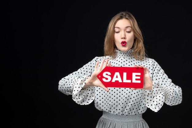 Vooraanzicht jonge mooie vrouw met verkoop schrijven op zwarte muur model schoonheid emotie mode vrouw kleur