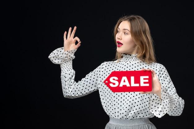 Vooraanzicht jonge mooie vrouw met verkoop schrijven op zwarte muur model schoonheid emotie rood winkelen mode vrouw kleuren