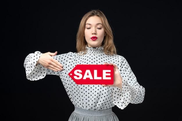 Vooraanzicht jonge mooie vrouw met verkoop schrijven op zwarte muur model schoonheid emotie winkelen mode vrouw kleur rood