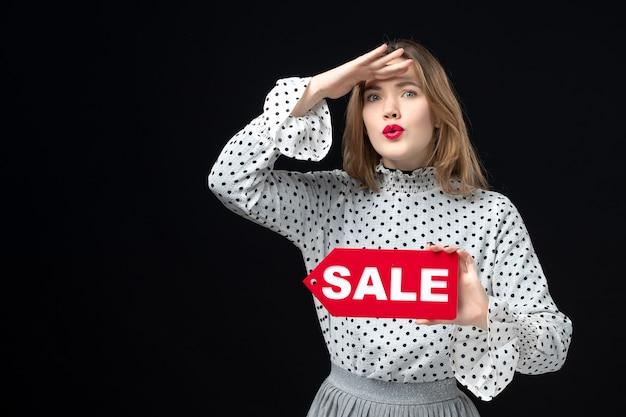 Vooraanzicht jonge mooie vrouw met verkoop schrijven op zwarte muur model schoonheid emotie winkelen mode vrouw kleuren rood
