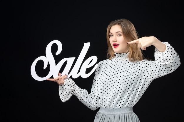 Vooraanzicht jonge mooie vrouw met verkoop schrijven op zwarte muur schoonheid mode emotie kleur model foto